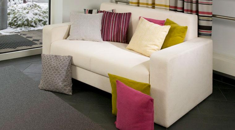 Weiße Couch mit bezogenen Kissen